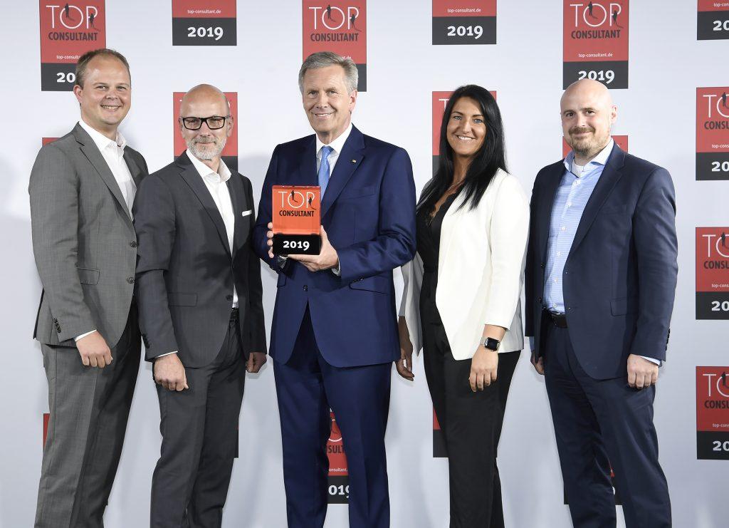 Bundespräsident a.D. Christian Wulff übergibt die Auszeichnung an Nico Lüdemann, Christian Meetz, Inga Knoche und Torben Volkmann